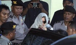 Schapelle Corby covers her head with a scarf as she is escorted by Indonesian police officers outside a parole office in Bali.