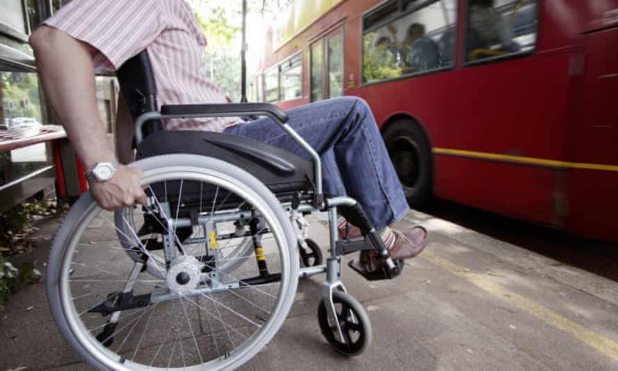 Disabled man in wheelchair getting on bus.