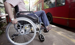 A man in a wheelchair at a London bus stop.