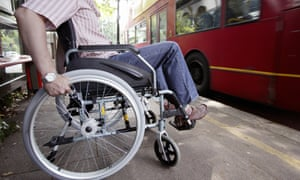 A man in wheelchair at a bus stop in London.
