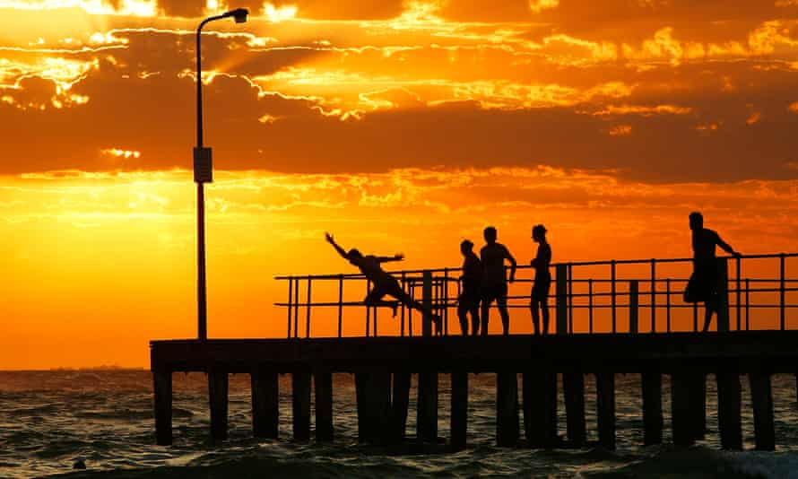 silhouettes of people diving off a pier against an orange cloudy sky