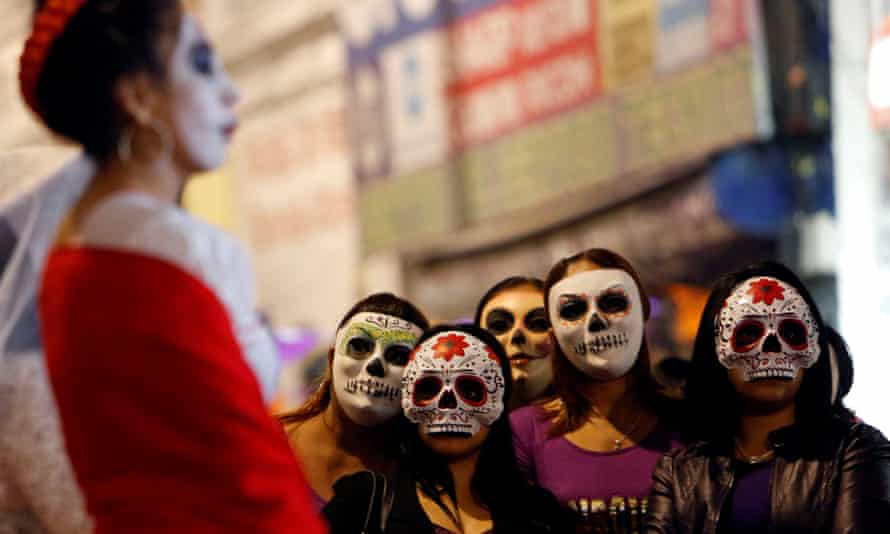 Women wear skeleton masks during a procession organized by sex workers to remember their deceased colleagues ahead of the Day of the Dead parade