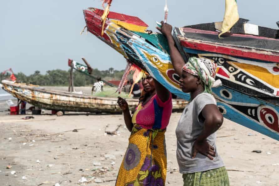 Fish traders Isatou Darboe (left) and Matida Jobewait for fishing boats to arrive, in Gunjur village