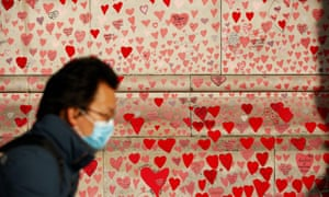 A man wearing a face mask passes the the national Covid memorial wall in London.