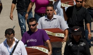 Relatives carry the coffins with the remains of their children during a mass funeral in Barranquilla on 11 September 2010 after Colombian authorities turned over the corpses of six victims of the army's 'false positives' scandal.