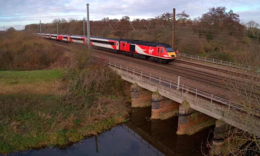 a virgin train approaches a bridge
