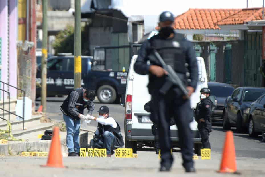 Police officers work at a crime scene where gunmen killed at least 13 Mexican police officers in an ambush, in Coatepec Harinas.