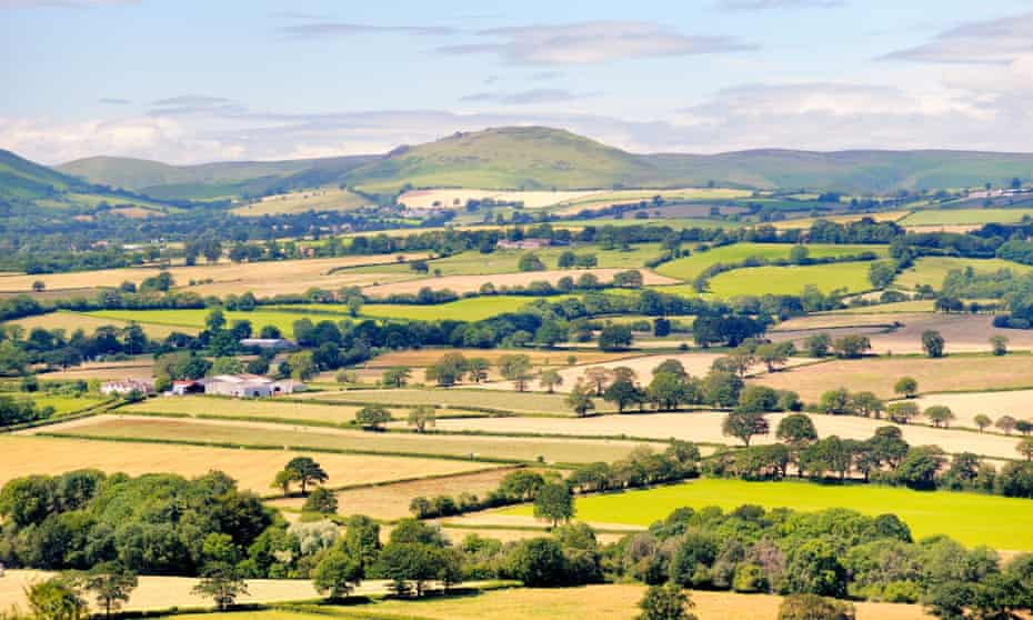 Looking south west from Wenlock Edge near Easthope over summer farmland of Ape Dale to Caer Caradoc and the Long Mynd, Shropshire