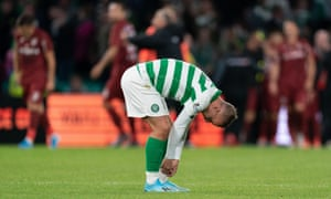 Leigh Griffiths of Celtic removes tape from his socks as CFR Cluj players celebrate in the background.