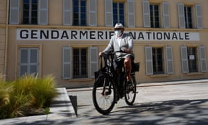 A man wearing a protective face mask rides his bike in front of the famous Gendarmerie of Saint-Tropez, 14 April .