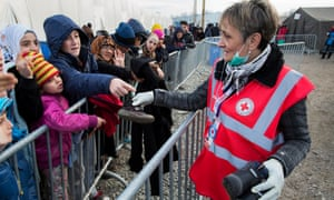 A Red Cross volunteer distributes clothing to recently arrived refugees, predominantly from Syria, Iraq and Afghanistan, at Slavonski Brod.