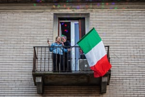 People plays various musical instruments and objects from their windows and balconies during a musical flash mob in Milan