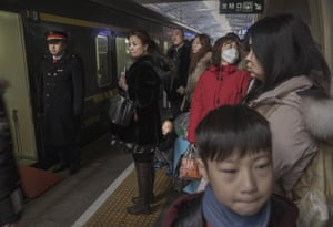 Travelers wait to board a train for 'standing room' passengers