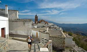 An woman with backpack walks in the Spanish village of Laroles in the Alpujarras