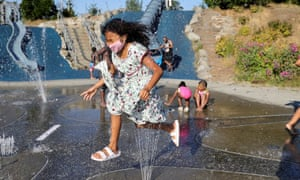 Isis Macadaeg, age 7, plays in a spray park at Jefferson Park during a heat wave in Seattle, Washington.