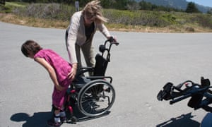 Mom helping her seven-year-old daughter with muscular dystrophy sit in her wheel chair