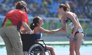 New Zealand's Nikki Hamblin, right, clasps arms with USA's Abbey D'Agostino as she is carried on a wheelchair from the finish line.