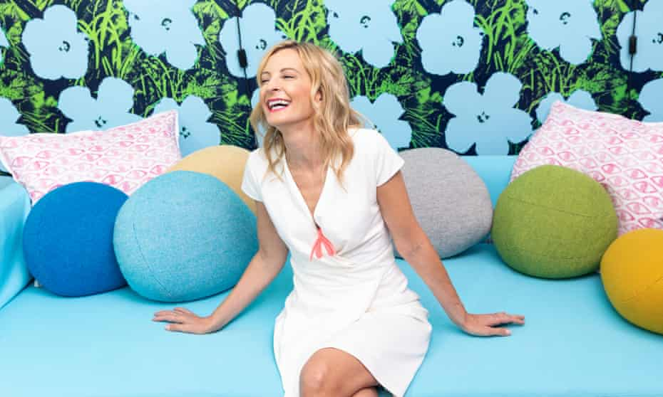Wednesday Martin in a white dress and wearing a clitoris shaped necklace, sitting on a pale blue sofa with round coloured cushions