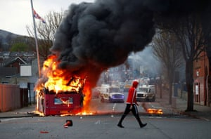 Belfast, Northern IrelandA man walks past a hijacked bus burning on the Shankill Road as protests continue