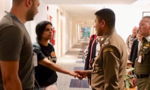 Saudi teenager Rahaf Mohammed al-Qunun (second from left) is greeted by Thai immigration authorities at a hotel inside Suvarnabhumi Airport in Bangkok.
