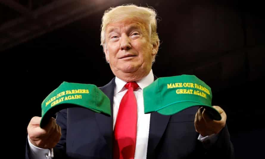 Trump with a 'Make Our Farmers Great Again' hat at an Indiana rally in August. Last year Trump told workers in upstate New York they should move elsewhere.