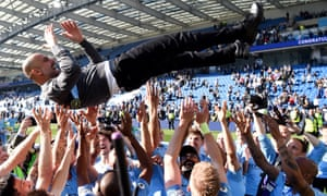 Brighton, England. Manchester City players throw manager Pep Guardiola in the air as they celebrate winning the Premier League title after trouncing Brighton.