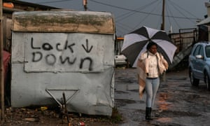 A woman walks past graffiti in Masiphumelele township in Cape Town, South Africa