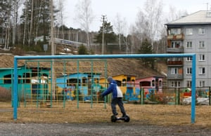 A boy rides a gyro-scooter near a goalpost on a pitch in the Siberian town of Divnogorsk