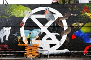 An Extinction Rebellion logo by Jane Mutiny is painted onto the side of a building in London