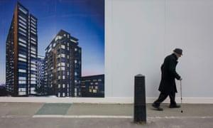 An elderly man walks bent past a regeneration project hoarding image at Elephant & Castle, London.
