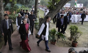 India's Congress party president Sonia Gandhi, front center and her son and party vice-president Rahul Gandhi, right, arrive at party headquarters after returning from court in Delhi on Saturday.