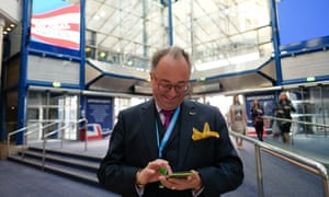 A delegate checks his phone inside the International Convention Centre in Birmingham.