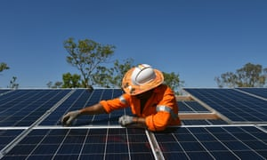 A worker installs solar panels in Daly River, Northern Territory.