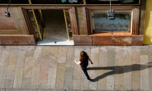 Aerial view of a woman walking into a Spanish shop