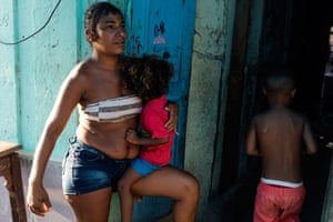 """29/01/2019: Fabiola holds her son on the porch where she was shot while pregnant with him three years ago. She was rushed to a health centre, where she remembers waking up in a pool of blood. She named the boy Moises, """"as he too had crossed a bloody river"""". Now, Fabiola is worried because the closest public health clinic is closing due to funding cuts, and the private clinics are unaffordable. """"What will I do if I have an emergency?"""" she asks. Almost everyone in her building has suffered from a virus transmitted by mosquitoes and they will be even more vulnerable without access to healthcare."""