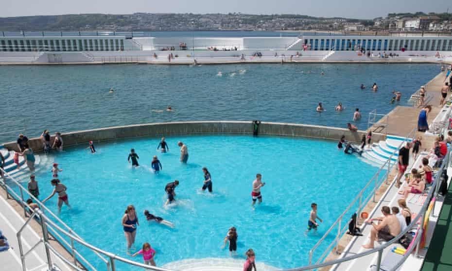 Visitors swim and sunbathe at Penzance Lido, Cornwall, UK