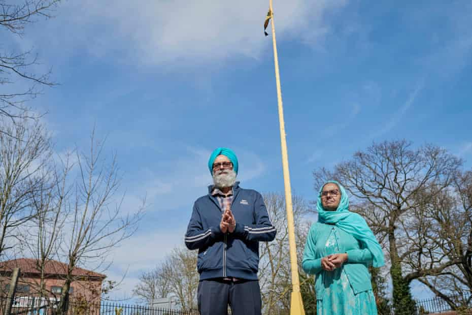 My parents in Slough outside their local temple, Ramgarhia Sikh gurdwara. Behind them is the sacred Khanda flag, a sign for all Sikhs and people from other faiths that they can come and pray in this building