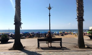 Holidaymaker on a bench near the beach at Santa Maria di Castellabate, Italy