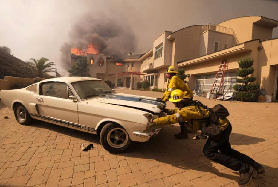 Firefighters push a car from a garage as a home burns in Malibu.