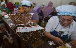 Indonesian women hand roll clove cigarettes at a factory in Malang