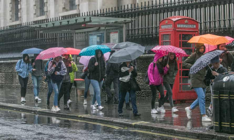 People brave the heavy rain in Trafalgar Square on a cold and wet Monday.