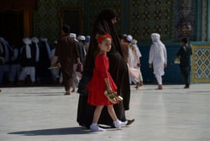 A girl walks with her mother through the courtyard of Hazrat Ali shrine, or Blue Mosque, in Mazar-i-Sharif, Afghanistan