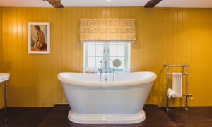 A yolk-yellow bathroom with a white rolltop bathtub in the middle of the room