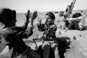 Iraqi children playing on a destroyed tank in 2003
