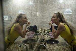 Jessica Hahn-Chaplin from Bristol, England, applies makeup before a rehearsal of the Paraíso de Tuiuti samba school in Rio de Janeiro
