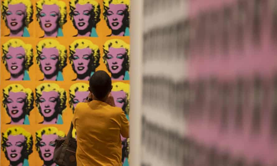 A visitor wearing a face mask views artworks by Andy Warhol during an exhibition at Tate Modern.
