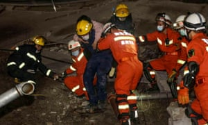 A woman is rescued from the rubble of a collapsed hotel in Quanzhou, in China's eastern Fujian province, on Saturday. About 70 people were trapped after the Xinjia hotel collapsed.