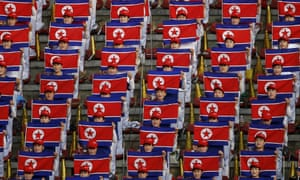North Korean fans hold flags and sing national anthem before a football match against Philippines at the Kim Il-sung Stadium in Pyongyang on Wednesday. The teams drew 1-1.