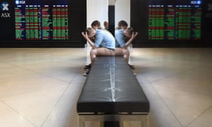 People are reflected in a mirror as they sit in front of a screen displaying market data on the Australian Stock Exchange