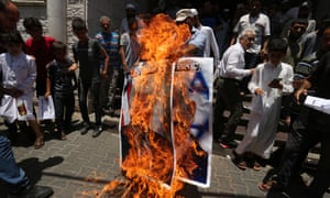 Palestinians burn a poster of Donald Trump